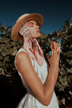 Greta Larosa WOMAN IN SCARF AND STRAW HAT BY VINES Women
