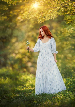 Lilia Alvarado GIRL WITH RED HAIR HOLDING FLOWER IN SUNLIT COUNTRYSIDE Women