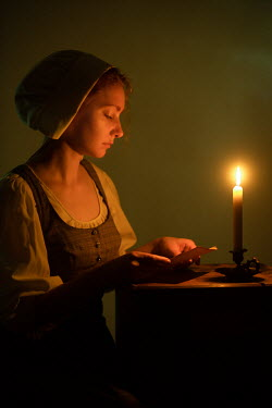 Magdalena Russocka historical maid reading by candlelight