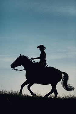 Magdalena Russocka young girl in cowboy outfit riding horse in field