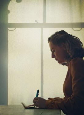 Mark Owen BLONDE WOMAN WRITING INDOORS BY WINDOW Women