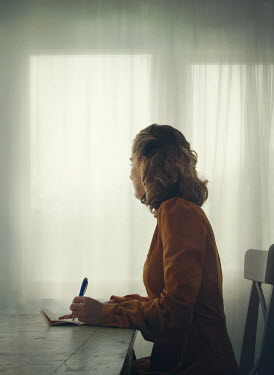 Mark Owen BLONDE WOMAN SITTING WRITING INDOORS BY WINDOW Women