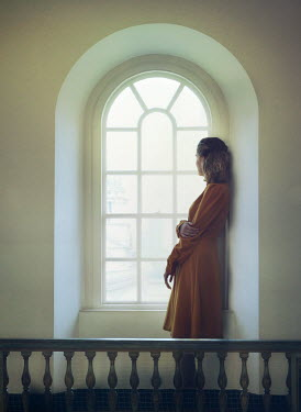 Mark Owen DAYDREAMING BLONDE WOMAN STANDING INDOORS BY WINDOW Women