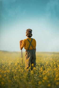 Ildiko Neer Land girl leaning on rake in rape field