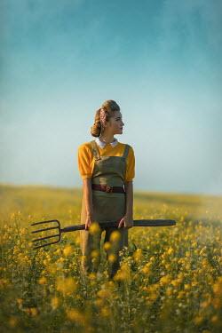 Ildiko Neer Land girl holding pitchfork in rape field