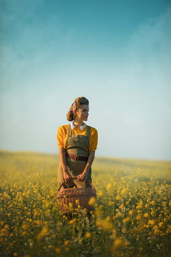 Ildiko Neer Land girl holding basket in rape field