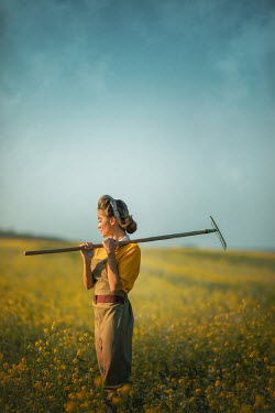 Ildiko Neer Land girl with rake on shoulder standing in rape field