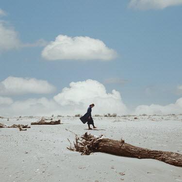 Felicia Simion WOMAN WALKING ON SANDY BEACH WITH DRIFTWOOD Women