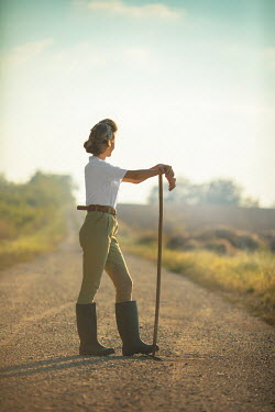 Ildiko Neer Land girl leaning on rake on country road Women
