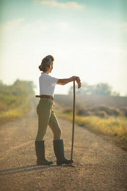 Ildiko Neer Land girl leaning on rake on country road Women