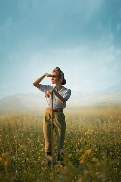 Ildiko Neer Land girl leaning on rake in rape field