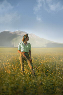 Ildiko Neer Land girl standing in rape field with rake