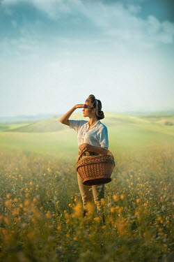 Ildiko Neer Land girl holding basket in rape field