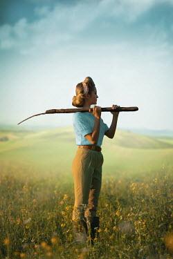 Ildiko Neer Land girl with pitchfork on shoulder standing in rape field