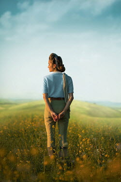 Ildiko Neer Land girl standing in rape field with cord on shoulder