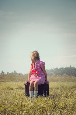 Joanna Czogala BLONDE LITTLE GIRL SITTING ON SUITCASE IN COUNTRYSIDE Children