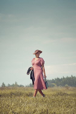 Joanna Czogala RETRO WOMAN IN HAT WALKING IN COUNTRYSIDE Women