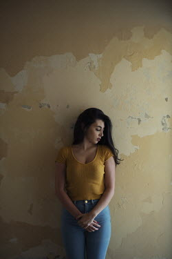 Mohamad Itani GIRL IN JEANS LEANING AGAINST TEXTURED WALL Women
