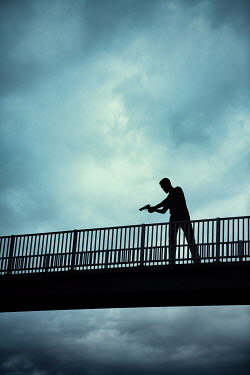Magdalena Russocka SILHOUETTED MAN WITH GUN ON BRIDGE Men