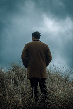 Rekha Garton MAN WITH COAT IN DUNES WITH STORMY SKY Men