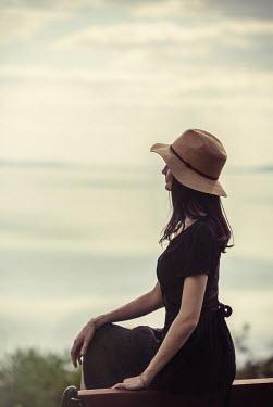 Nikaa WOMAN IN HAT SITTING WATCHING SEA Women