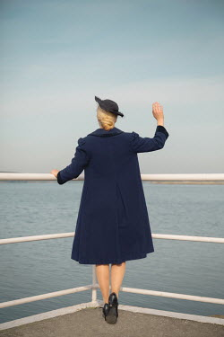 Joanna Czogala BLONDE RETRO WOMAN WAVING BY RAILINGS WITH SEA SEA Women