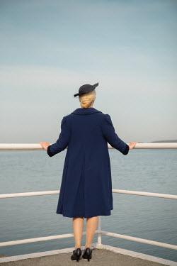 Joanna Czogala RETRO WOMAN IN HAT BY RAILINGS WATCHING SEA Women