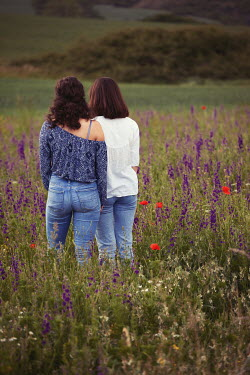 Kerstin Marinov TWO BRUNETTE WOMEN STANDING IN FIELD WITH FLOWERS Women