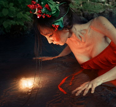 Kirill Sakryukin ASIAN WOMAN WITH BERRIES WATCHING LIGHT IN WATER Women