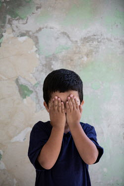Mohamad Itani LITTLE BOY COVERING EYES IN SHABBY ROOM Children