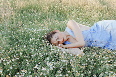Felicia Simion GIRL IN DENIM DRESS LYING IN FIELD WITH DAISIES Women