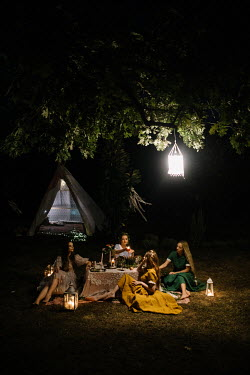 Jovana Rikalo FEMALE GROUP SITTING BY TENT AT NIGHT Groups/Crowds
