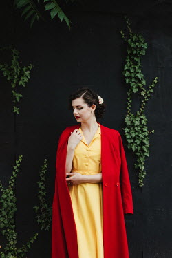 Matilda Delves WOMAN IN RED COAT STANDING BY WALL WITH IVY Women