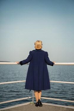 Joanna Czogala BLONDE RETRO WOMAN STANDING BY RAILINGS WATCHING SEA Women