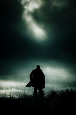 Nic Skerten SILHOUETTED MAN WALKING IN FIELD AT NIGHT Men