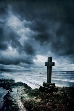 Silas Manhood STONE CRUCIFIX ON BEACH WITH STORMY SKY Statuary/Gravestones