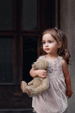 Kerstin Marinov LITTLE GIRL HOLDING TEDDY BY DOORWAY OUTDOORS Children