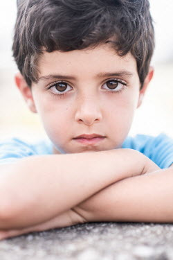 Mohamad Itani SAD LITTLE BOY WITH DARK HAIR LEANING ON WALL Children