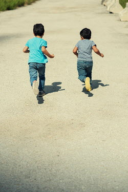 Mohamad Itani TWO LITTLE BOYS RUNNING ON ROAD IN SUMMER Children