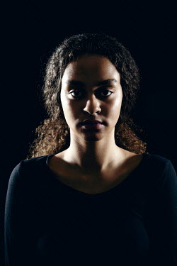 Miguel Sobreira Woman With Curly Hair Pulled Back in Shadows