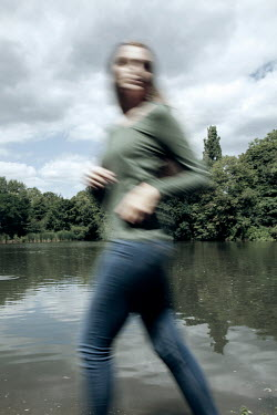 Miguel Sobreira BLURRED WOMAN RUNNING BY LAKE IN SUMMER Women