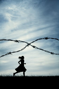 Magdalena Russocka silhouette of woman wearing dress running behind barbed wire