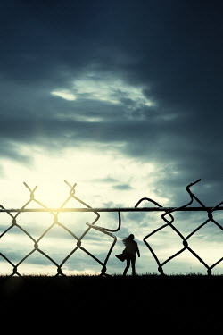 Magdalena Russocka silhouette of modern woman running behind wire fence