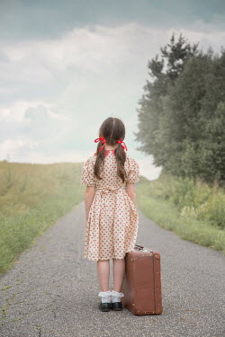 Joanna Czogala Girl with suitcase standing on rural road