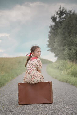 Joanna Czogala Girl with suitcase sitting on rural road