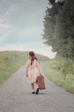Joanna Czogala Girl with suitcase walking on rural road