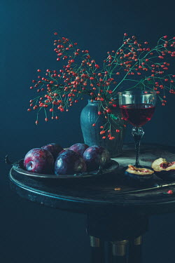 Magdalena Wasiczek Branches with berries, glass of red wine, and plate of plums