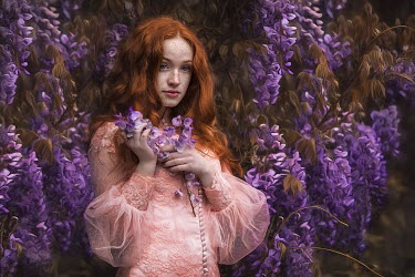Beata Banach Young woman in pink dress under wisteria tree
