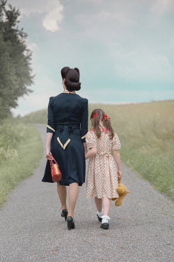 Joanna Czogala Woman and her daughter walking on rural road