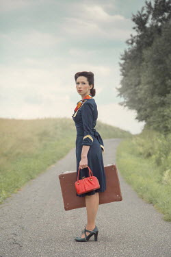 Joanna Czogala Young woman with suitcase walking on rural road